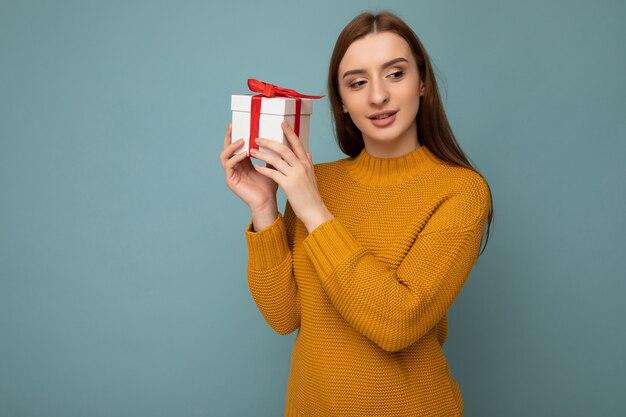 Fotoaufnahme einer schönen, glücklichen, brünetten jungen frau, die über einer blauen hintergrundwand isoliert ist und einen senffarbenen pullover trägt, der eine weiße geschenkbox mit rotem band hält und zur seite schaut