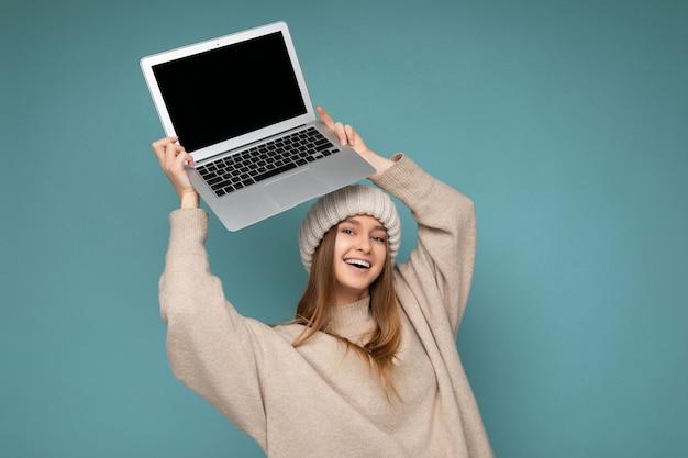 Fotoaufnahme einer schönen jungen dunkelblonden frau mit glattem haar in warmer gestrickter beige mütze des winters