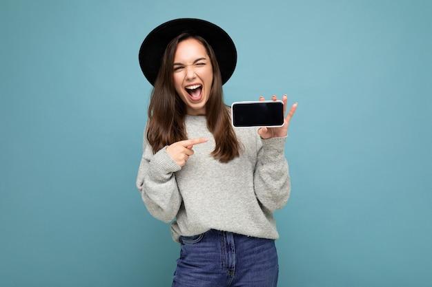 Fotoaufnahme einer schönen jungen frau mit schwarzem hut und grauem pullover, die das telefon mit dem smartphone zeigt, das auf dem hintergrund isoliert ist. mock-up, ausschnitt, kopienraum