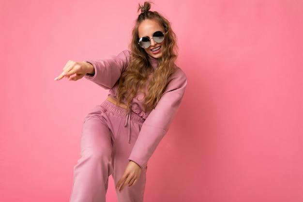 Fotoaufnahme einer schönen jungen positiven dunkelblonden frau, die freizeitkleidung und eine stilvolle sonnenbrille trägt, die auf buntem hintergrund isoliert ist und in die kamera schaut