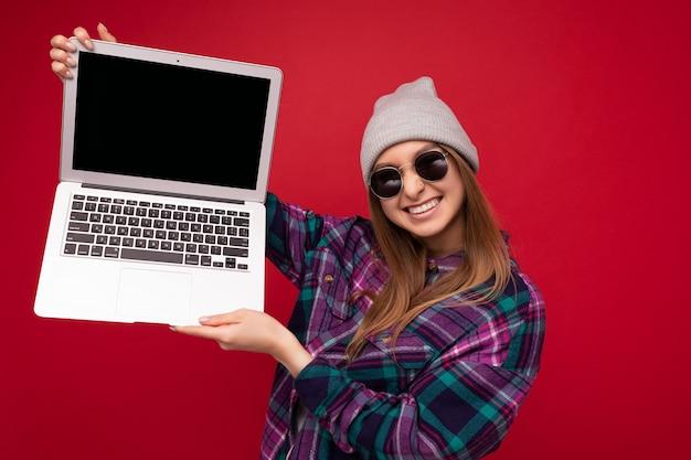 Fotoaufnahme einer schönen lächelnden dunkelblonden jungen frau, die computer-laptop mit leerem monitor hält holding