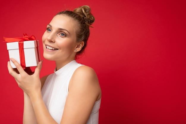Fotoaufnahme einer schönen, positiv lächelnden jungen blonden frau, die über einer roten hintergrundwand isoliert ist und ein weißes oberteil trägt, das eine geschenkbox hält und zur seite schaut. platz kopieren, mockup