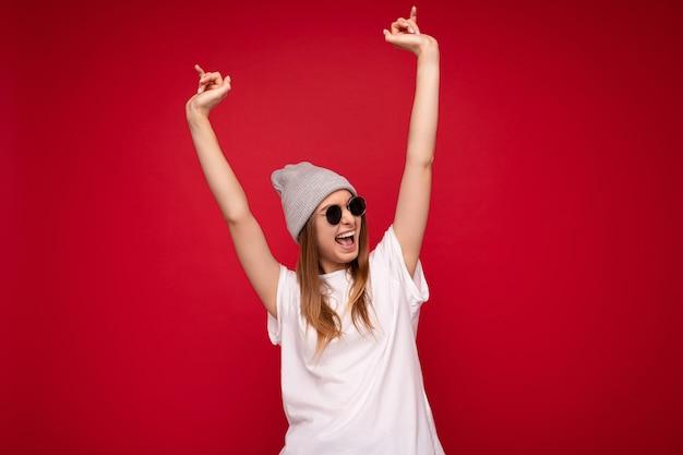 Fotoaufnahme einer schönen positiv lächelnden jungen dunkelblonden frau, die auf rotem hintergrund isoliert ist und ein lässiges weißes t-shirt mit grauem hut für ein modell und eine stilvolle sonnenbrille trägt, die zur seite schaut und spaß hat