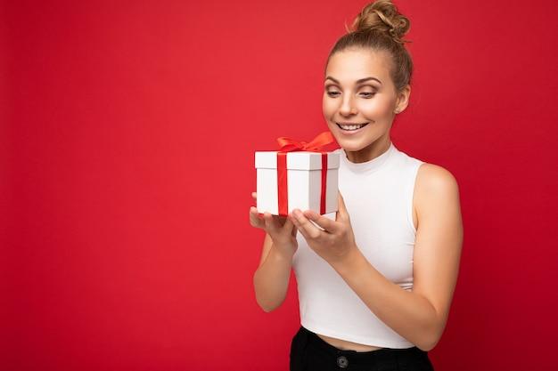 Fotoaufnahme einer schönen, positiv lächelnden, überraschten jungen blonden frau, die über einer roten hintergrundwand isoliert ist und ein weißes oberteil trägt, das geschenkbox hält und derzeit aussieht. freiraum