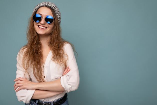 Fotoaufnahme einer schönen positiven jungen blonden frau, die freizeitkleidung und eine stilvolle optische brille trägt, die über einer bunten hintergrundwand mit blick auf die kamera isoliert ist. platz kopieren
