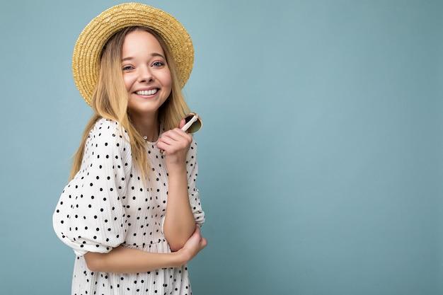 Fotoaufnahme einer schönen positiven jungen blonden frau, die sommerliche freizeitkleidung trägt und hält