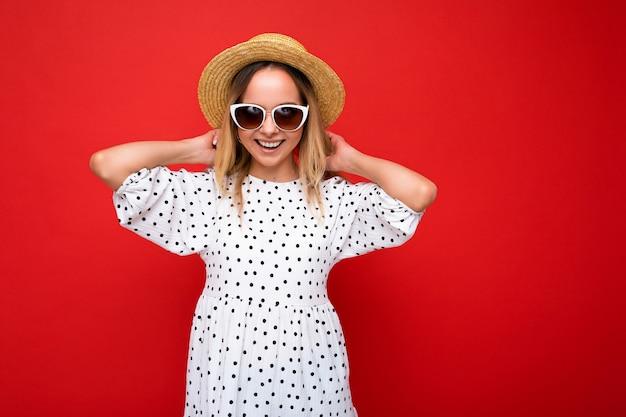 Fotoaufnahme einer schönen positiven jungen blonden frau, die sommerliche freizeitkleidung trägt und stylisch