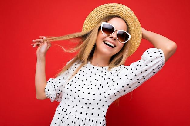 Fotoaufnahme einer schönen positiven jungen blonden frau, die sommerliche freizeitkleidung und eine stilvolle sonnenbrille trägt, die auf buntem hintergrund isoliert ist und zur seite schaut