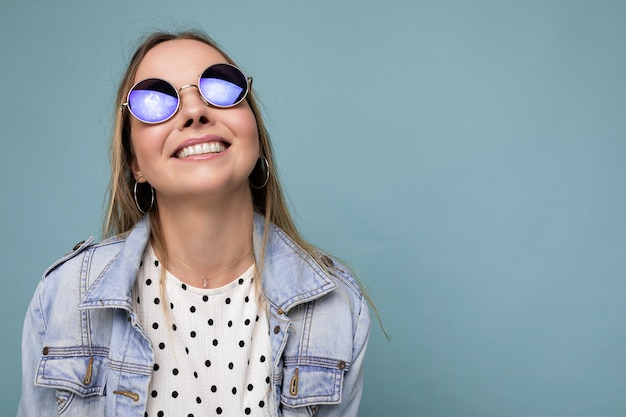 Fotoaufnahme einer schönen, positiven jungen blonden frau, die sommerliche freizeitkleidung und eine stilvolle sonnenbrille trägt, die auf buntem hintergrund mit blick auf die kamera isoliert ist. freiraum