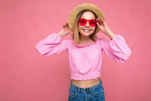 Fotoaufnahme einer schönen, positiven jungen blonden frau, die sommerliche freizeitkleidung und eine stilvolle sonnenbrille trägt, die auf buntem hintergrund mit blick auf die kamera isoliert ist.