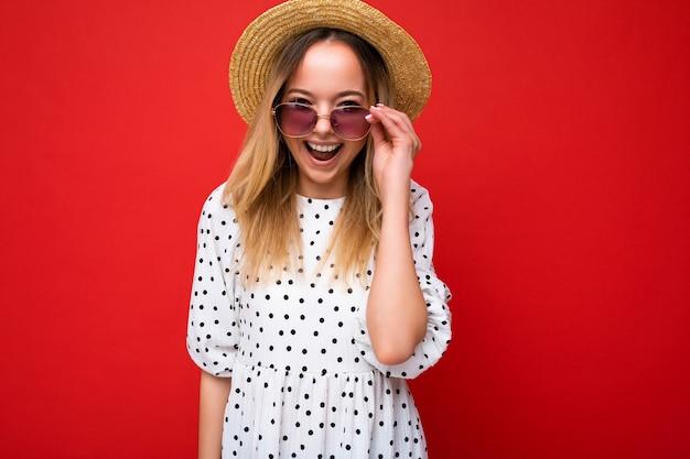 Fotoaufnahme einer schönen positiven jungen blonden frau, die sommerliche freizeitkleidung und eine stilvolle sonnenbrille trägt, die auf buntem hintergrund mit blick auf die kamera isoliert ist