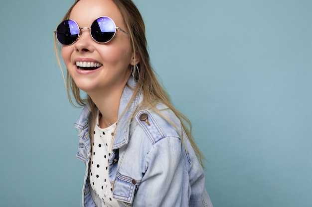 Fotoaufnahme einer schönen positiven jungen blonden frau, die sommerliche freizeitkleidung und eine stilvolle sonnenbrille trägt, die auf buntem hintergrund mit blick auf die kamera isoliert ist.