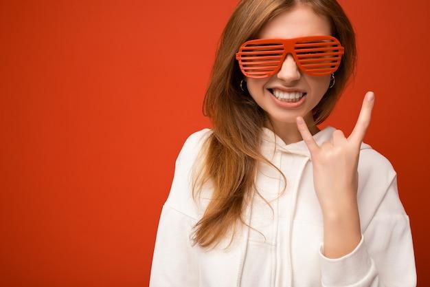 Fotoaufnahme einer schönen positiven jungen blonden frau in freizeitkleidung und stilvoller optik