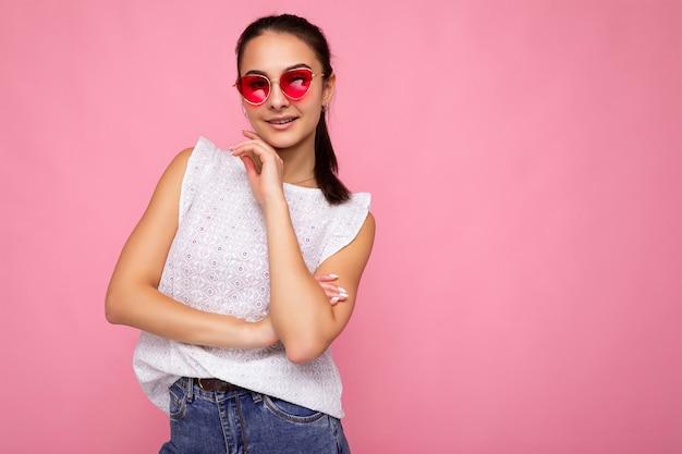 Fotoaufnahme einer schönen positiven jungen brünetten frau, die sommerliche freizeitkleidung und eine stilvolle sonnenbrille trägt, die über einer bunten hintergrundwand mit blick auf die kamera isoliert ist. platz kopieren