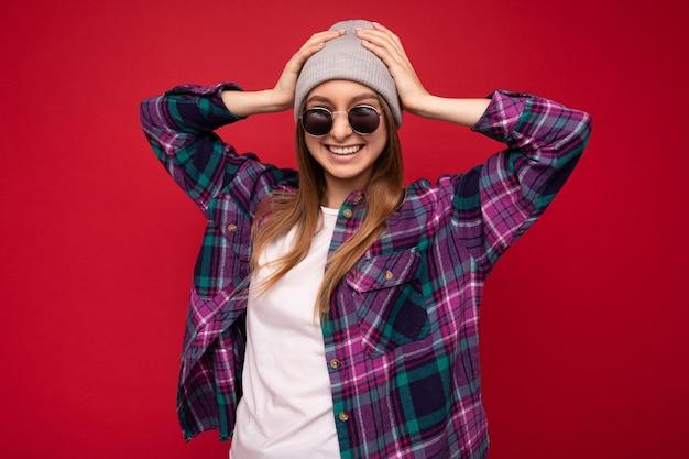 Fotoaufnahme einer schönen positiven jungen brünetten frau, die sommerliche freizeitkleidung und eine stilvolle sonnenbrille trägt, die über einer bunten hintergrundwand mit blick auf die kamera isoliert ist.