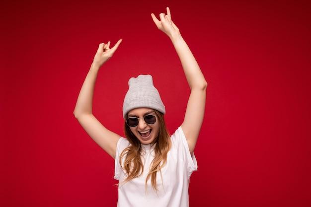 Fotoaufnahme einer schönen positiven jungen dunkelblonden frau, die freizeitkleidung trägt und stylisch