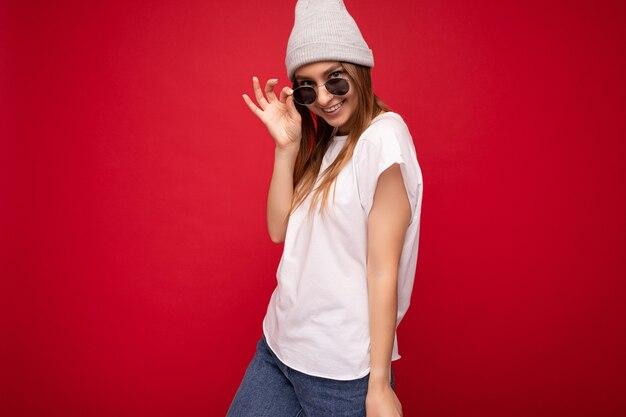 Fotoaufnahme einer schönen sexy jungen dunkelblonden frau, die auf rotem hintergrund isoliert ist und ein lässiges weißes t-shirt für ein modell und eine stilvolle sonnenbrille trägt, die in die kamera schaut. platz kopieren