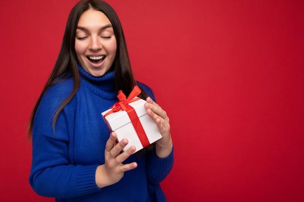Fotoaufnahme einer ziemlich positiv überraschten jungen brunet-frau, die über einer bunten hintergrundwand isoliert ist und einen trendigen outfit-look trägt, der eine geschenkbox hält und die geschenkbox mit rotem band betrachtet. freiraum