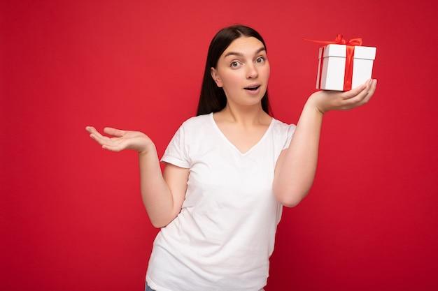 Fotoaufnahme einer ziemlich positiv überraschten jungen brunet-frau, die über einer bunten hintergrundwand isoliert ist und einen trendigen outfit-look trägt, der eine geschenkbox hält und in die kamera schaut.