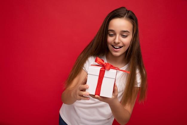 Fotoaufnahme eines attraktiven, glücklich lächelnden brünetten mädchens, das über roter hintergrundwand isoliert ist und ein weißes t-shirt trägt, das weiße geschenkbox mit rotem band hält und derzeit aussieht.