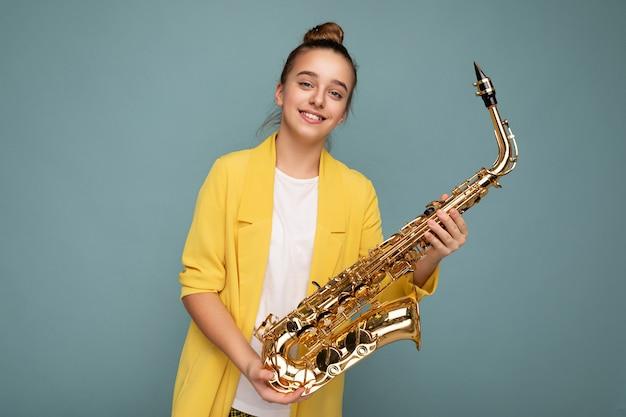 Fotoaufnahme eines attraktiven, positiv lächelnden, brünetten kleinen mädchens, das eine trendige gelbe jacke trägt, die isoliert über einer blauen hintergrundwand steht und saxophon mit blick auf die kamera hält.