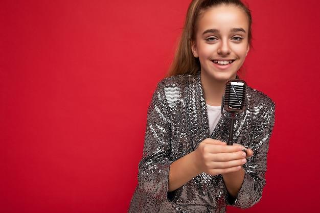 Fotoaufnahme eines glücklich lächelnden brünetten kleinen weiblichen teenagers, der modische glanzkleidung trägt, die isoliert über einer roten hintergrundwand steht und ein silbernes mikrofon zum singen von liedern mit blick auf die kamera hält.