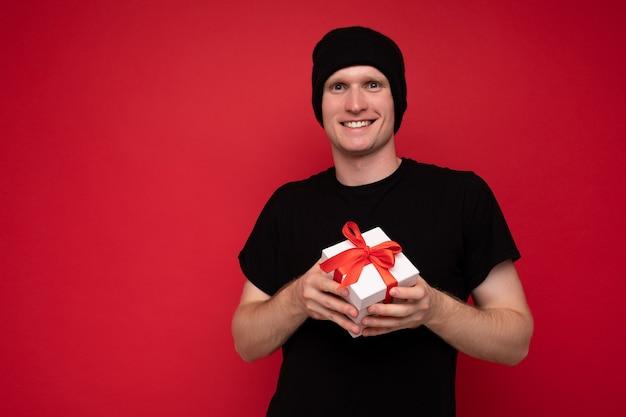 Fotoaufnahme eines gutaussehenden, positiv lächelnden jungen mannes, der über einer roten hintergrundwand isoliert ist und einen schwarzen hut und ein schwarzes t-shirt trägt, das eine weiße geschenkbox mit rotem band hält und in die kamera schaut.