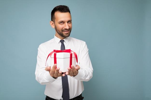 Fotoaufnahme eines gutaussehenden, positiven, brünetten jungen, unrasierten mannes mit bart isoliert über blauer hintergrundwand, der ein weißes hemd und eine krawatte trägt, die weiße geschenkbox mit rotem band hält und in die kamera schaut