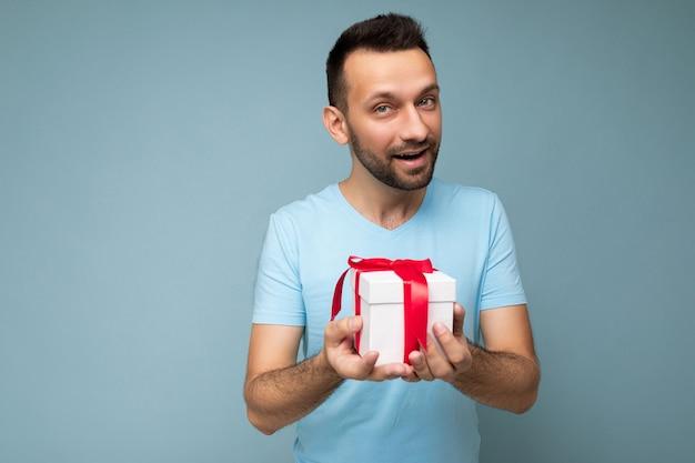 Fotoaufnahme eines gutaussehenden, positiven, unrasierten jungen mannes, der über einer blauen hintergrundwand isoliert ist und ein blaues t-shirt trägt, das eine weiße geschenkbox mit rotem band hält und in die kamera schaut