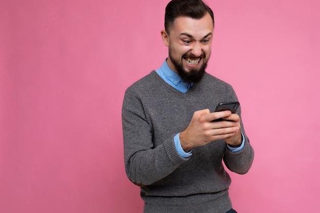 Fotoaufnahme eines gutaussehenden, überglücklichen, emotionalen, gut aussehenden jungen mannes, der lässig stylisch trägt