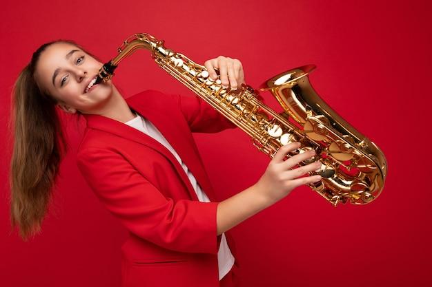 Fotoaufnahme eines hübschen, glücklich lächelnden, brünetten kleinen mädchens, das eine stylische rote jacke trägt, die isoliert über einer roten hintergrundwand steht und saxophon mit blick auf die kamera spielt.