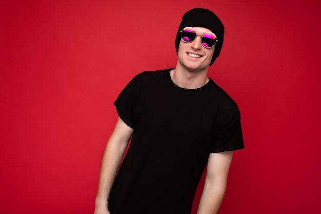 Fotoaufnahme eines hübschen, glücklich lächelnden jungen mannes, der ein lässiges schwarzes t-shirt trägt