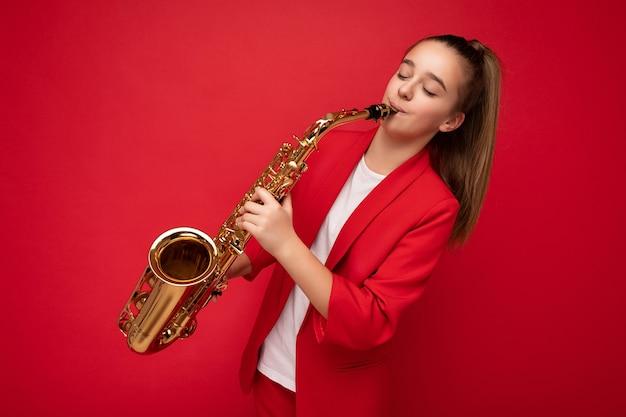 Fotoaufnahme eines hübschen, glücklichen, brünetten kleinen weiblichen teenagers, der eine stylische rote jacke trägt