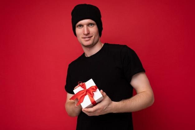Fotoaufnahme eines hübschen, glücklichen jungen mannes, der über einer roten hintergrundwand isoliert ist und einen schwarzen hut und ein schwarzes t-shirt trägt, das eine weiße geschenkbox mit rotem band hält und in die kamera schaut.