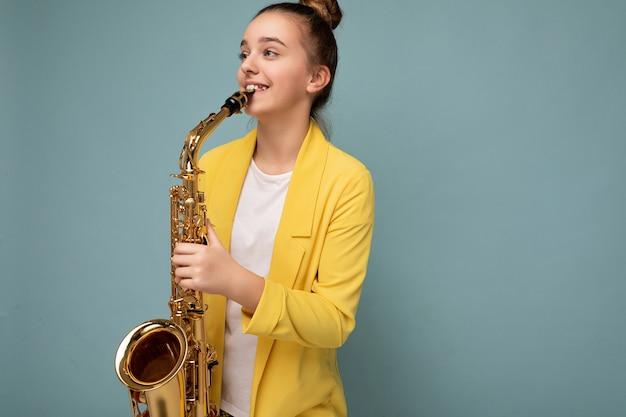 Fotoaufnahme eines hübschen, positiv lächelnden, brünetten kleinen mädchens, das eine trendige gelbe jacke trägt, die isoliert über einer blauen hintergrundwand steht und saxophon spielt, das zur seite schaut.