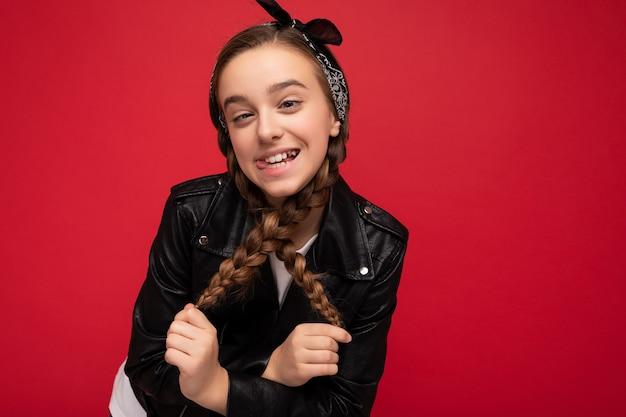 Fotoaufnahme eines hübschen, positiv lächelnden, brünetten, kleinen weiblichen teenagers mit zöpfen, der eine stilvolle schwarze lederjacke und ein weißes t-shirt trägt, das isoliert über einer roten hintergrundwand steht und in die kamera schaut.