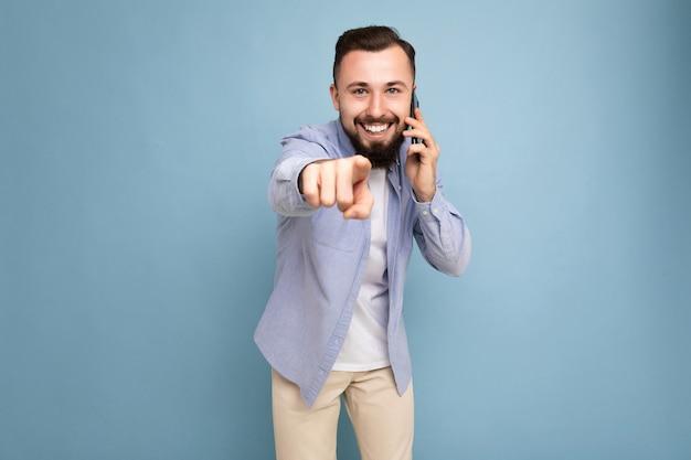 Fotoaufnahme eines positiv lächelnden, gut aussehenden jungen bärtigen mannes mit lässigem blauem hemd und