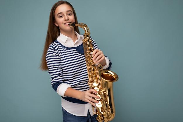 Fotoaufnahme eines schönen, glücklich lächelnden, brünetten mädchens, das gestreiftes langarmshirt trägt, das isoliert über blauer hintergrundwand steht und saxophon mit blick auf die kamera spielt. platz kopieren