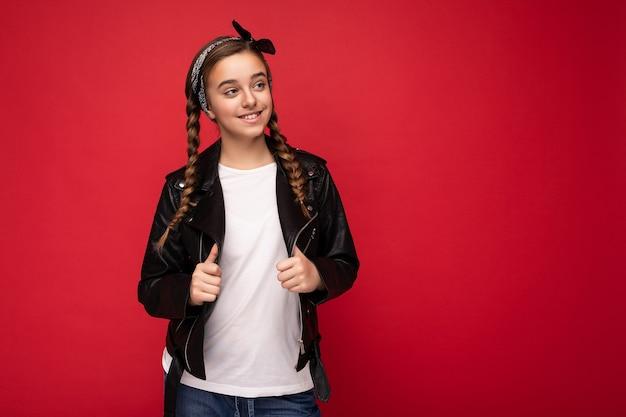 Fotoaufnahme eines schönen, glücklich lächelnden, brünetten mädchens mit zöpfen, das eine trendige schwarze lederjacke und ein weißes t-shirt für das modell trägt, das isoliert über einer roten hintergrundwand steht und zur seite schaut