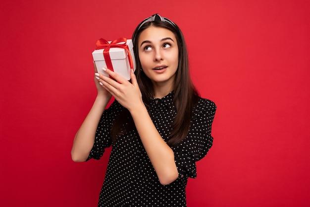 Fotoaufnahme eines schönen, glücklichen, nachdenklichen brünetten mädchens, das über einer roten hintergrundwand isoliert ist und eine schwarze bluse trägt, die eine weiße geschenkbox mit rotem band hält und aufschaut und denkt.
