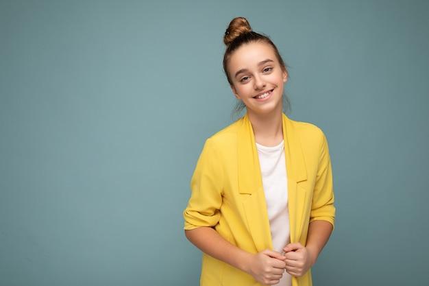 Fotoaufnahme eines schönen, positiv lächelnden, brünetten kleinen mädchens, das eine trendige gelbe jacke und ein weißes t-shirt trägt, das isoliert über der blauen hintergrundwand steht und in die kamera schaut