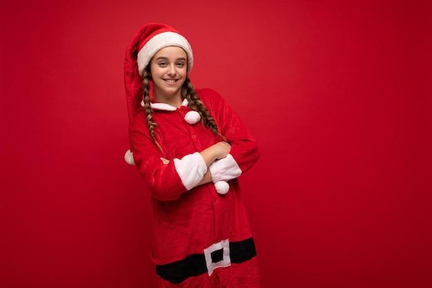 Fotoaufnahme eines ziemlich glücklichen, positiv lächelnden brünetten mädchens mit zöpfen, die weihnachtsmann-kleidung tragen