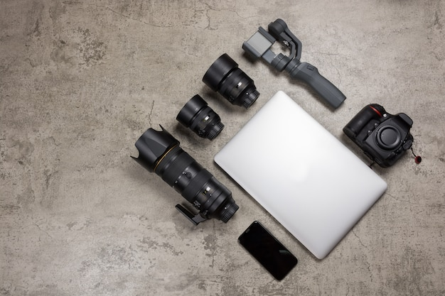 Fotoausrüstung zum reisen auf nacktem mörtelhintergrund, dslr-kamera, objektiven, laptop, maus und gimbal.