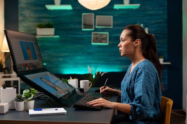 Fotobearbeitungsspezialist, der im künstlerischen studio mit bild auf dem computerdisplay arbeitet. fotografin, die den farbverlauf auf dem foto retuschiert, während sie das touchpad und den stift als werkzeuge verwendet