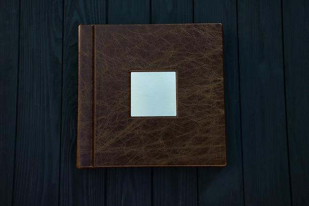 Fotobuch aus echtem braunem leder mit einem metallisch silbernen typenschild auf einem schwarzen holztisch.
