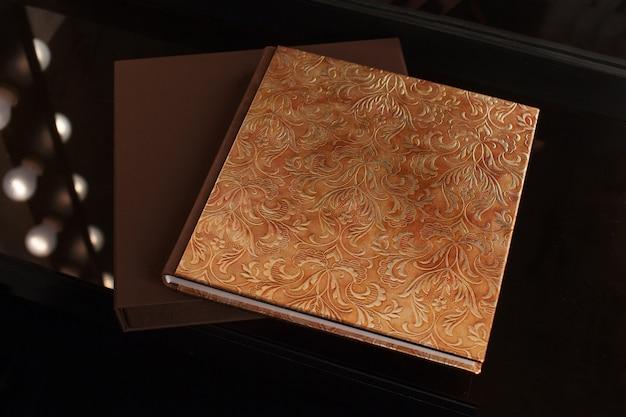 Fotobuch mit einem umschlag aus echtem leder. braune farbe mit dekorativer prägung. dunkler hintergrund. weicher fokus.