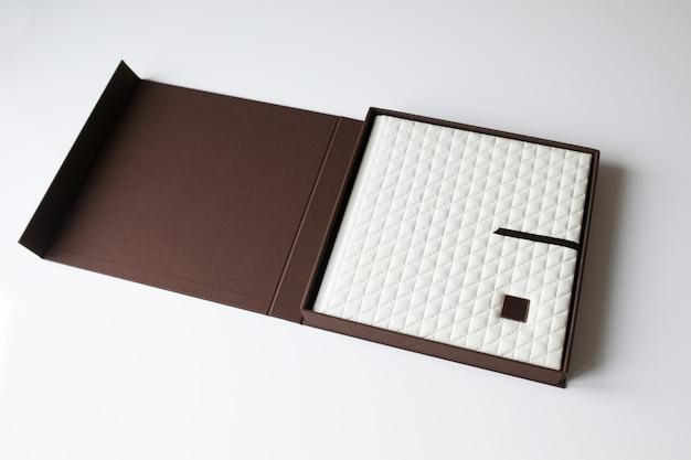 Fotobuch mit einem umschlag aus echtem leder in der box. weiße farbe mit dekorativer prägung. weicher fokus.