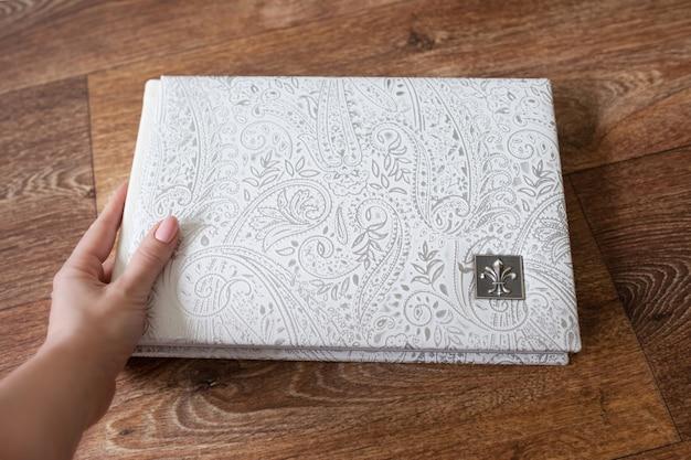 Fotobuch mit einem umschlag aus echtem leder. weiße farbe mit dekorativer prägung. fotobuch in frauenhand