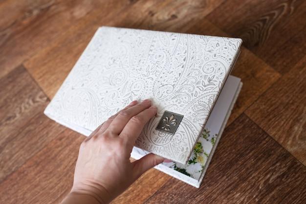 Fotobuch mit einem umschlag aus echtem leder. weiße farbe mit dekorativer prägung. hand öffnendes fotobuch