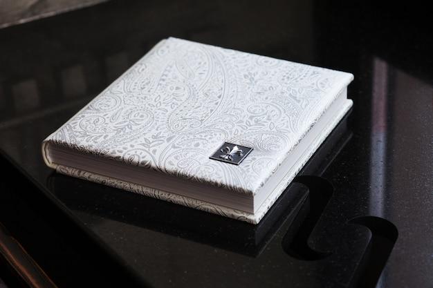 Fotobuch mit einem umschlag aus echtem leder. weiße farbe mit dekorativer prägung. hochzeits- oder familienfotoalbum. familienwert